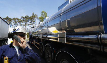refinery worker filling large fuel-truck inside refinery